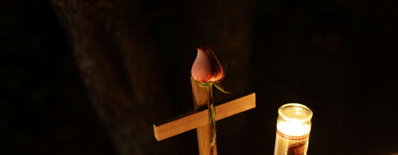 A rose is tied to a cross next to candles outside Saint Rose of Lima Roman Catholic Church near Sandy Hook Elementary School, where a gunman opened fire on school children and staff in Newtown, Connecticut December 14, 2012. A heavily armed gunman opened fire on school children and staff at a Connecticut elementary school on Friday, killing at least 28 people, including 20 children, in the latest in a series of shooting rampages that have tormented the United States this year. REUTERS/Joshua Lott (UNITED STATES - Tags: CRIME LAW EDUCATION)