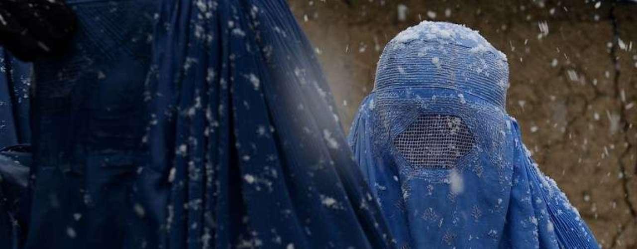Una mujer desplazada afgana espera las provisiones contra el invierno que entrega la ONU en un campo de refugiados de Kabul.