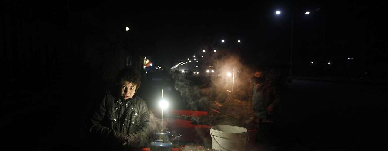 Un niño afgano vende sopa de pollo durante la noche en una calle de la parte antigua de la capital afgana.