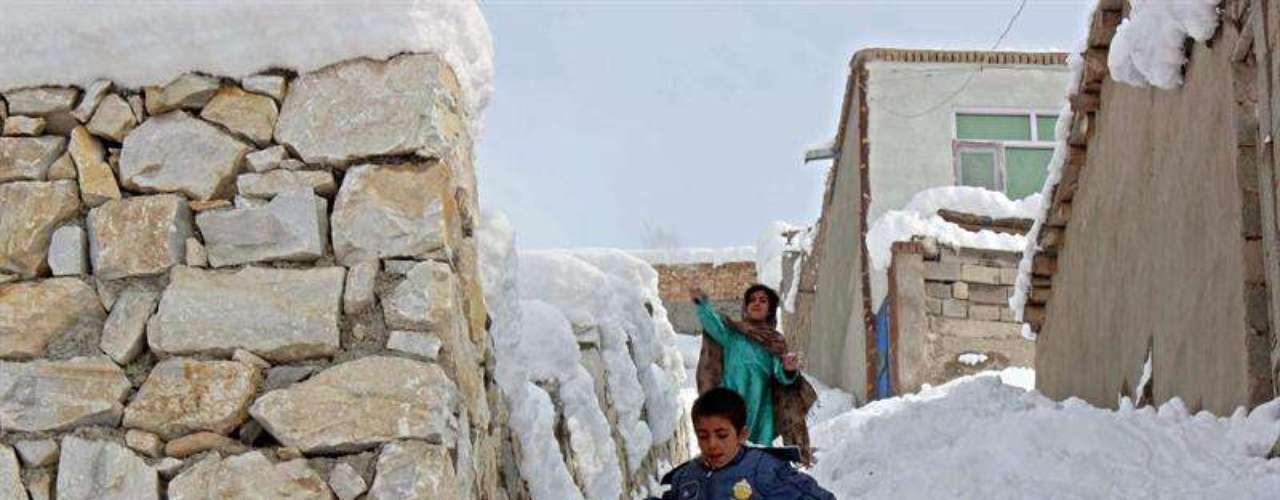 Un niño camina cargado entre la nieve en la capital afgana mientras otra menor lanza una bola.