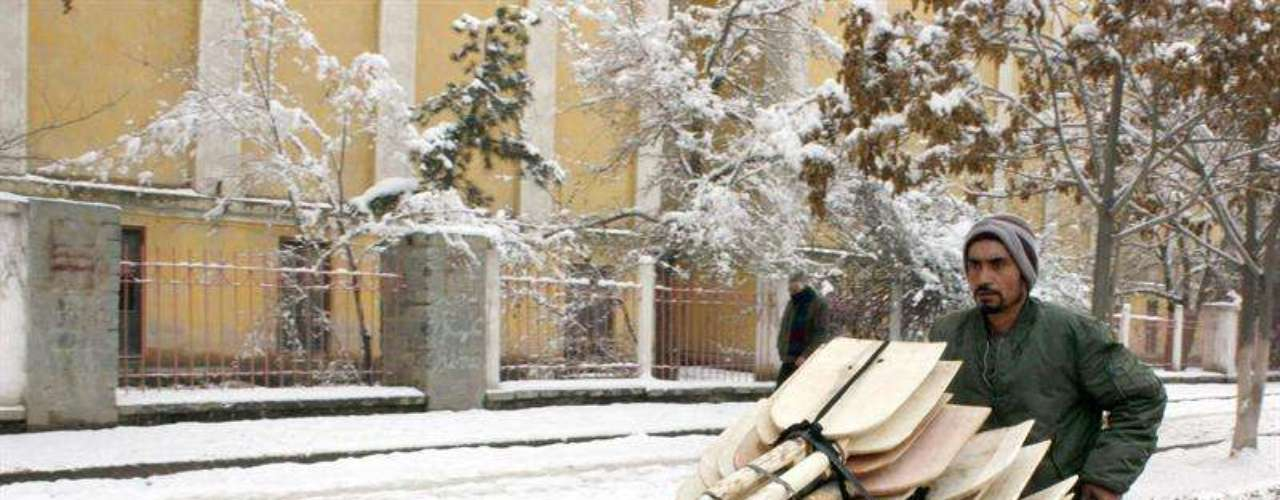 Un hombre traslada material pesado con una carretilla a través de la nieve que cubre Kabul.