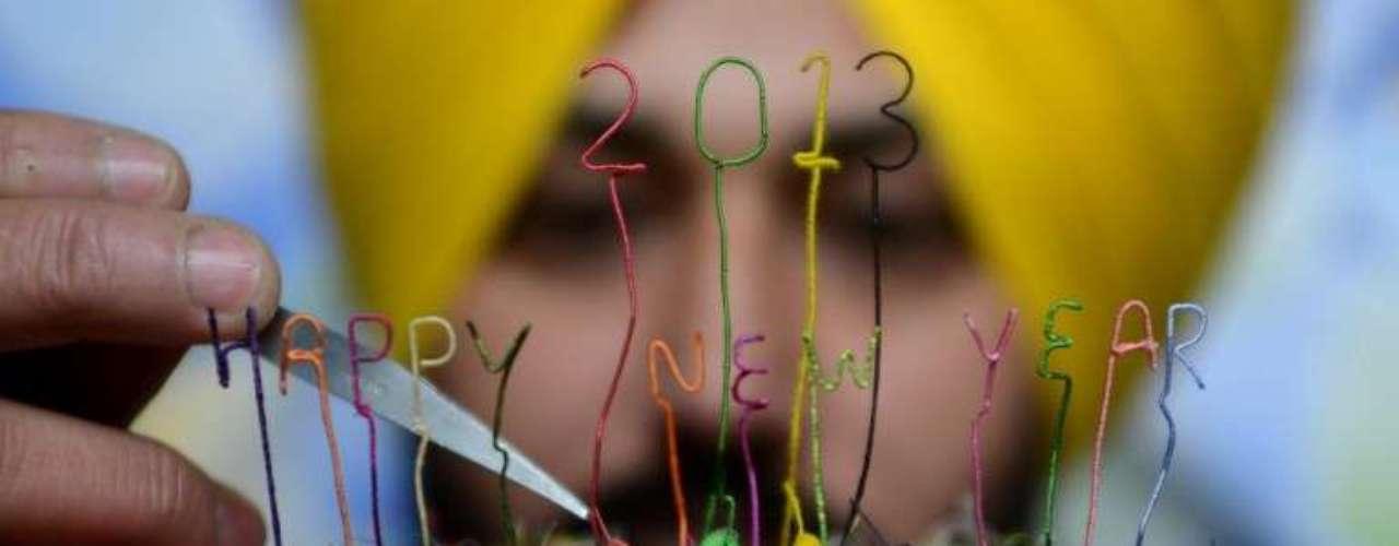 Un artista indio muestra una escultura creada para saludar la llegada del Año Nuevo.