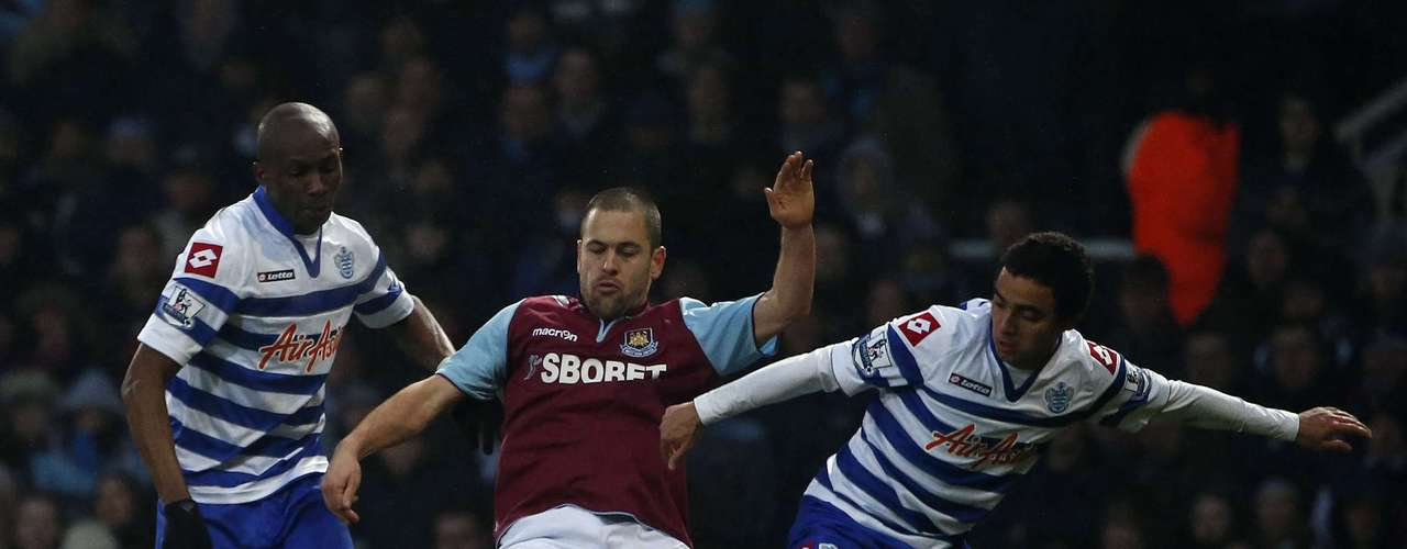 West Ham United's Joe Cole (C) is challenged by Queens Park Rangers' Stephane Mbia (L) and Fabio.