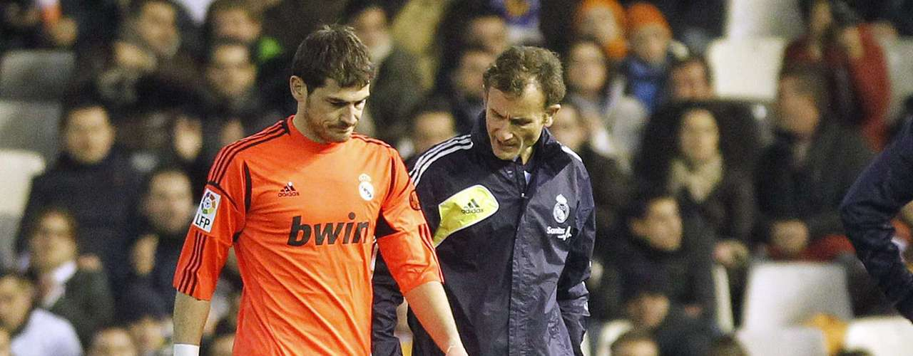 Real Madrid's goalkeeper Iker Casillas (L) leaves the pitch after injuring his hand. REUTERS/Heino Kalis
