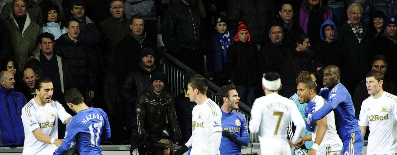 Swansea's Ashley Williams (3rd R) is held back as he tries to confront Chelsea's Eden Hazard (2nd L) as he collects the ball after kicking a ball boy during their English League Cup semi-final second leg soccer match at the Liberty Stadium in Swansea, January 23, 2013.