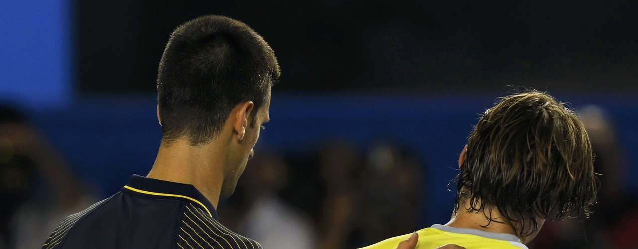 Novak Djokovic of Serbia (L) places his hand on the back of David Ferrer of Spain after defeating himin straight sets.