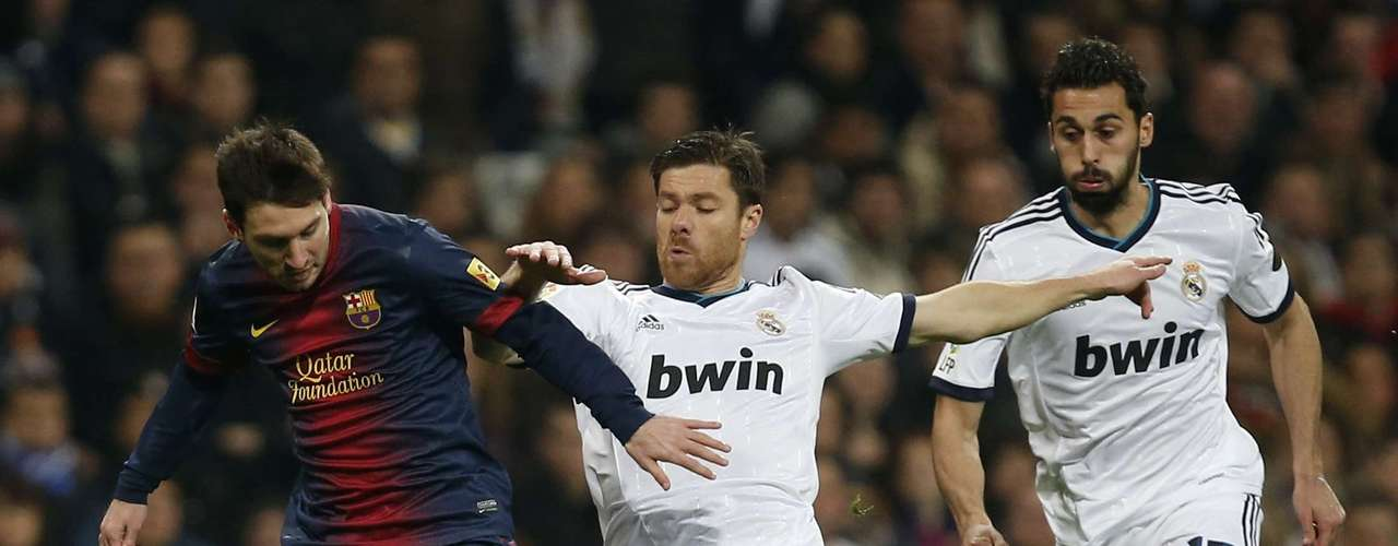 Lionel Messi is challenged by Xabi Alonso and Alvaro Arbeloa.4