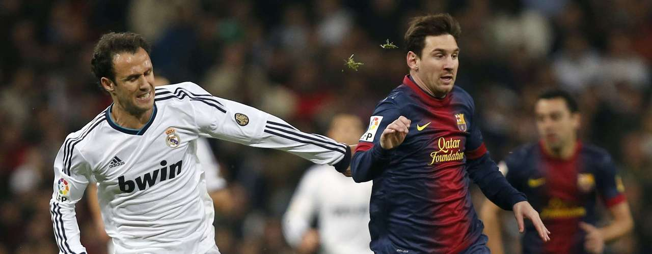 Ricardo Carvalho (L) fights for the ball with Lionel Messi.