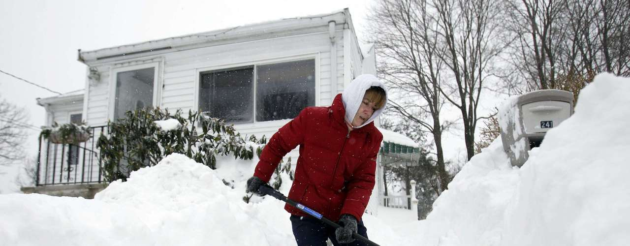Donnalyn Sullivan shovels out her front steps during a blizzard in Medford, Massachusetts February 9, 2013. A blizzard pummelled the Northeastern United States, killing at least one person, leaving hundreds of thousands without power and disrupting thousands of flights, media and officials said.  REUTERS/Jessica Rinaldi (UNITED STATES - Tags: ENVIRONMENT)