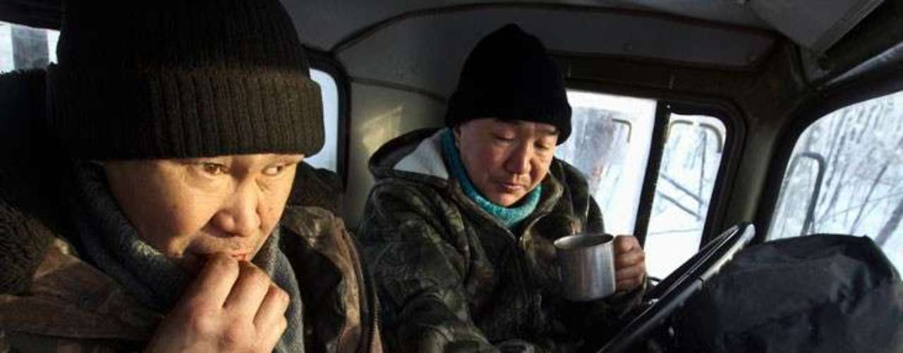 Timbers Alexey Egorov, 45, (L) and Semion Vinokurov, 53, have breakfast in a cabin at their truck outside of Tomtor.