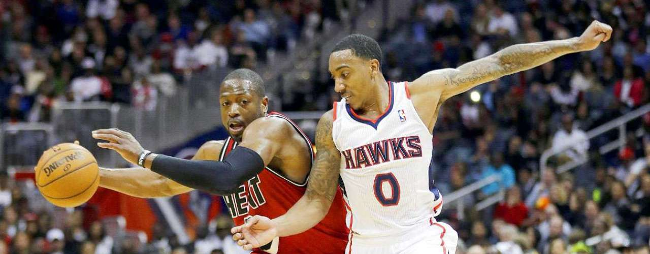 Heat vs. Hawks: Dwyane Wade (3) intenta quitarse la marca de Jeff Teague (0).