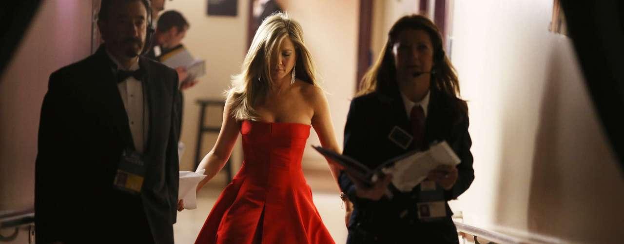 Jennifer Aniston camina muy segura hacia el escenario en su despampanante traje rojo, junto a dos productores, para anunciar el premio de la noche al mejor vestuario.