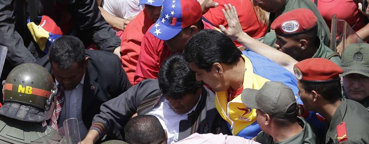 El vicepresidente venezolano Nicolás Maduro (con chaqueta amarilla) y el presidente boliviano Evo Morales (centro) avanzan entre una multitud el 6 de febrero del 2013, rodeados de soldados, tratando de llegar al hospital militar de Caracas donde falleció Hugo Chávez. (AP Photo/Ricardo Mazalan)