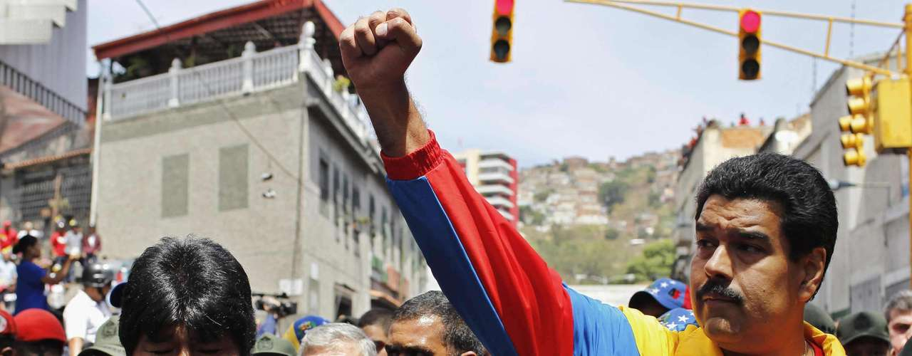 Venezuela's Vice President Nicolas Maduro (R) and Bolivia's President Evo Morales (L) walk ahead of the vehicle carrying the coffin of deceased Venezuelan leader Hugo Chavez, as it is driven through the streets of Caracas after leaving the military hospital where he died of cancer in Caracas, March 6, 2013. Authorities have not yet said where Chavez will be buried after his state funeral on Friday.     REUTERS/Carlos Garcia Rawlins (VENEZUELA - Tags: POLITICS OBITUARY)