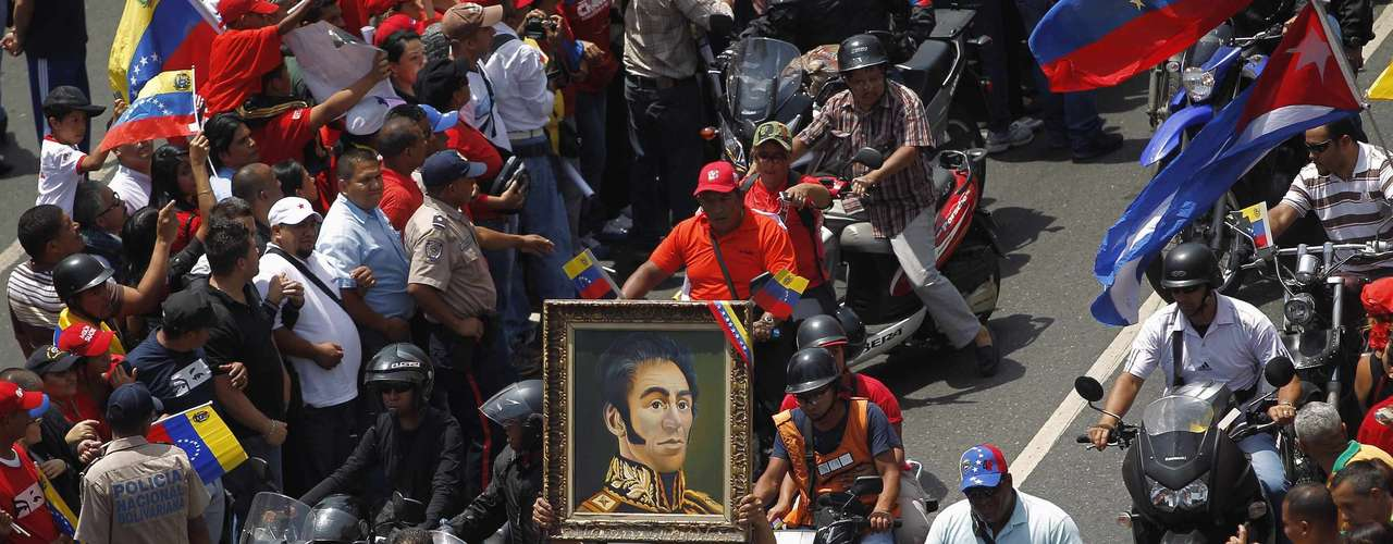 A supporter of Venezuela's late President Hugo Chavez carries a portrait of independence hero Simon Bolivar through a crowd waiting to see his coffin driven through the streets of Caracas, March 6, 2013. Chavez died on Tuesday of cancer, and authorities have not yet said where he will be buried after his state funeral on Friday.  REUTERS/Jorge Dan Lopez (VENEZUELA - Tags: POLITICS OBITUARY)