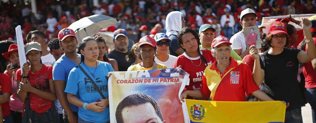 Supporters of Venezuela's late President Hugo Chavez watch as his coffin arrives at the Military Academy, where his wake will be held, in Caracas March 6, 2013. Authorities have not yet said where Chavez will be buried after his state funeral on Friday. REUTERS/Jorge Silva (VENEZUELA  - Tags: POLITICS OBITUARY)