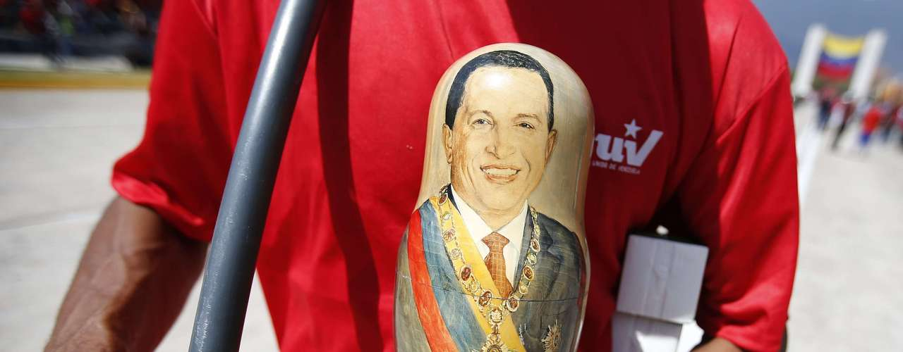A supporter of the late Venezuelan President Hugo Chavez holds an ornament painted with the likeness of his portrait, at the Military Academy where his wake will be held, in Caracas March 6, 2013. Ending one of Latin America's most remarkable populist rules, Chavez died on Tuesday at age 58 after a two-year battle with cancer that was first detected in his pelvis. Authorities have not yet said where his remains will be buried after his state funeral on Friday.          REUTERS/Jorge Silva (VENEZUELA  - Tags: POLITICS OBITUARY)
