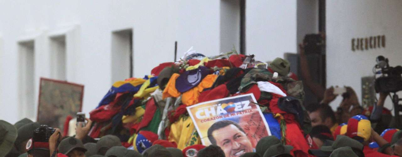The coffin of late Venezuelan leader Hugo Chavez covered with clothes that people have thrown at it, is driven through the streets of Caracas, after leaving the military hospital where he died of cancer, March 6, 2013. Authorities have not yet said where Chavez will be buried after his state funeral on Friday.    REUTERS/Edwin Montilva (VENEZUELA  - Tags: OBITUARY POLITICS)