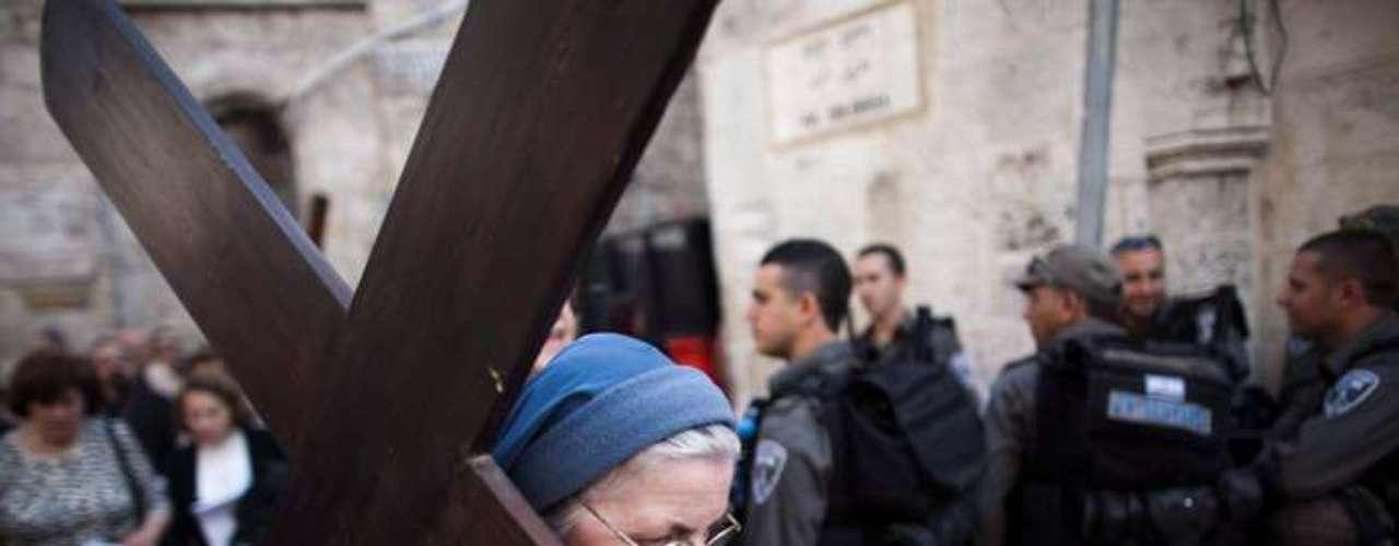 Una monja carga con una cruz mientras participa en el Vía Crucis del Viernes Santo por la Vía Dolorosa