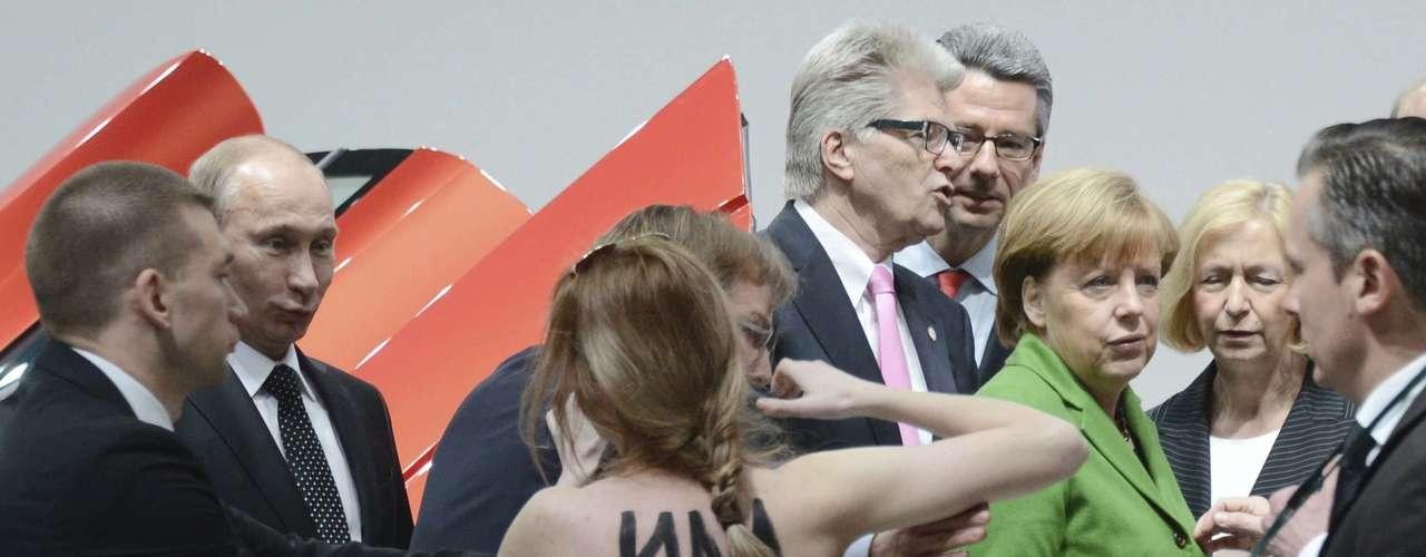 Las activistas del movimiento Femen aprovecharon la visita inaugural a la Feria de Putin y la canciller federal, Angela Merkel, para desnudarse de cintura para arriba ante los dos mandatarios y su séquito, que se vieron sorprendidos ante la acción de protesta.