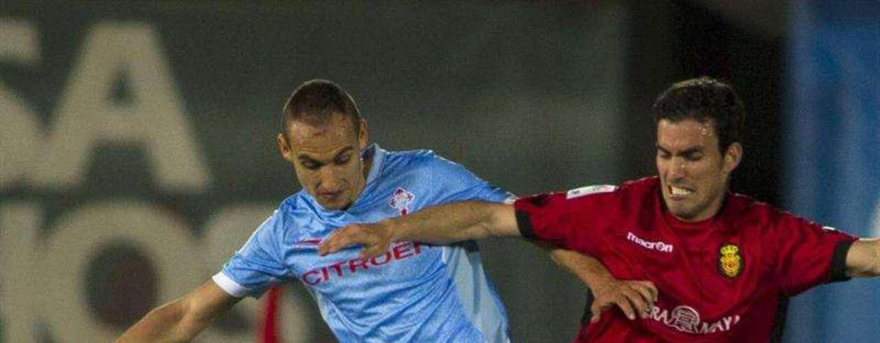 El defensa escocés del RCD Mallorca Alan Hutton (d) disputa el balón al central del Celta de Vigo Natxo Insa (i) durante el partido de la trigésimo primera jornada de Liga de Primera División que se juega esta noche en el Iberostar Estadio