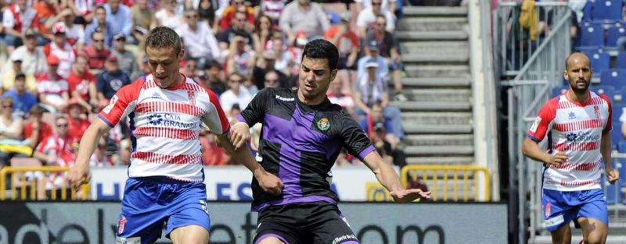 El centrocampista rumano del Granada Gabriel Andrei Torje (i) y el delantero del Valladolid Javier Guerra luchan por el balón durante el partido correspondiente a la trigésimo segunda jornada de liga que disputan en el Estadio de los Cármenes, en Granada
