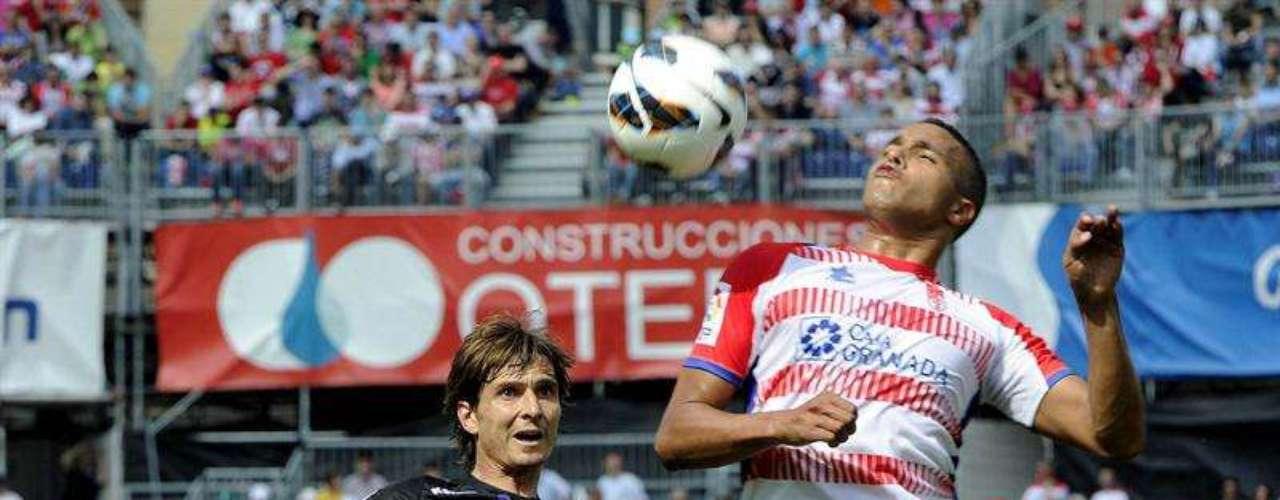 El delantero marroquí del Granada Youssef El-Arabi (d) lucha un balón con el centrocampista del Real Valladolid Álvaro Rubio durante el partido correspondiente a la trigésimo segunda jornada de liga que disputan en el Estadio de los Cármenes, en Granada.