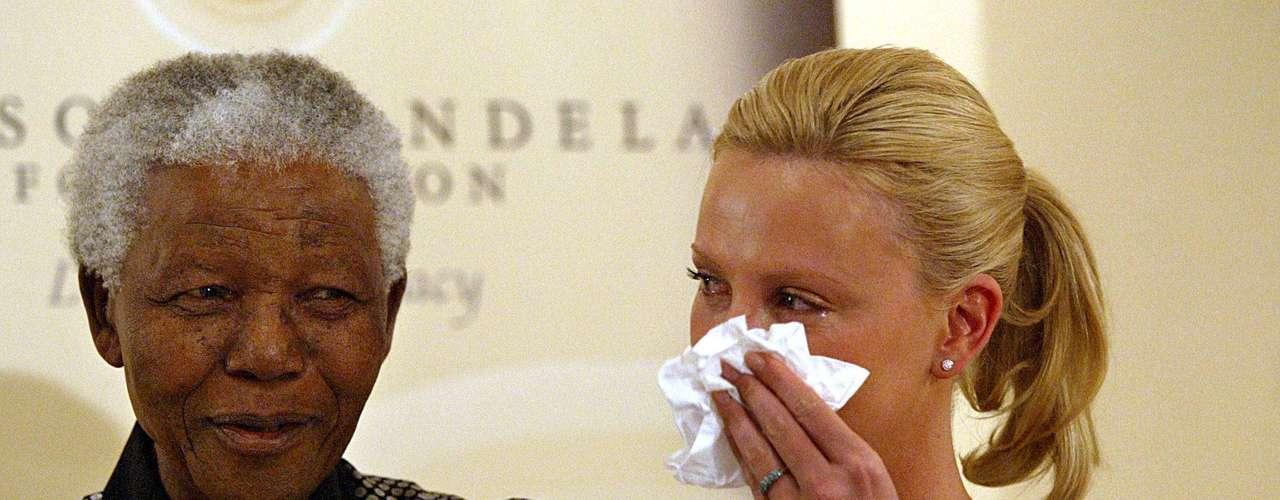 El líder sudafricano junto a su compatriota, la actriz Charlize Theron. 11 de marzo de 2004.