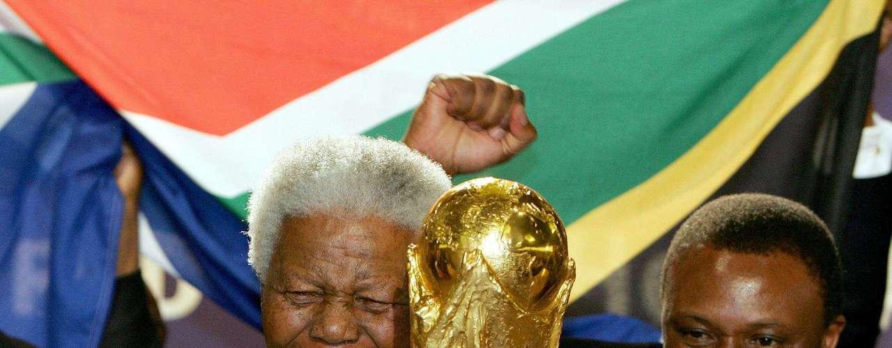 En junio de 2004, Mandela anunció su retiro de la vida pública con las palabras: No me llamen, yo los llamaré. Sin embargo, pasaron otros seis años hasta que pudiera retirarse por completo. En la imagen el ex presidente sudafricano alza la Copa del Mundo que se jugaría en Sudáfrica en 2010.