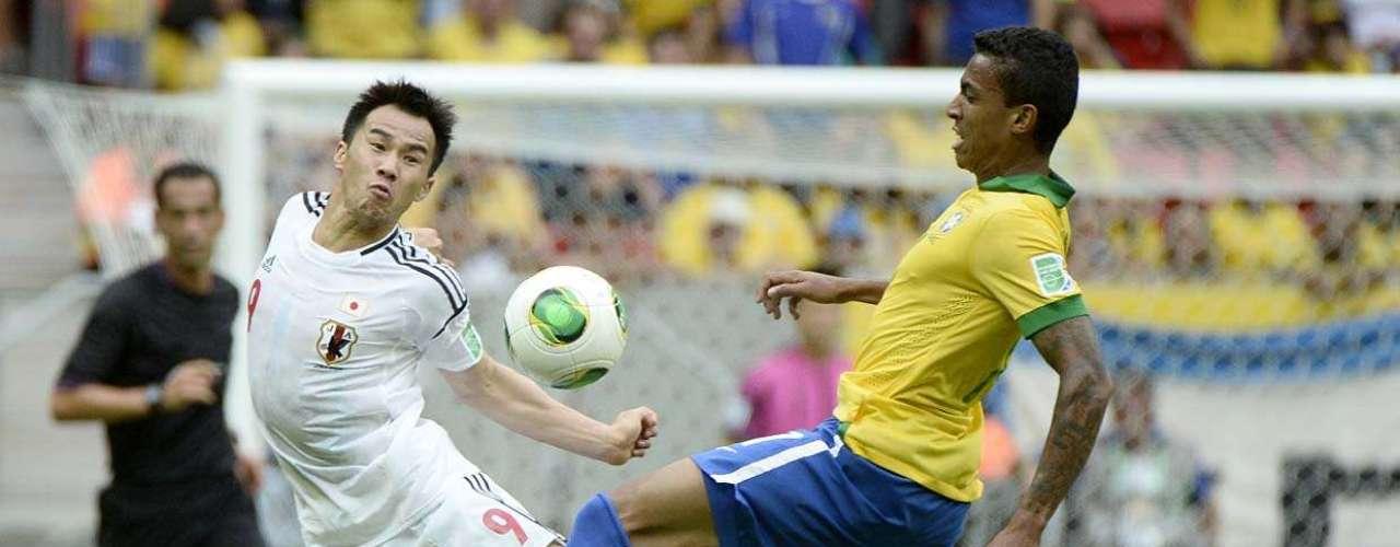 El mediocampista Luiz Gustavo domina la disputa con el delantero Shinji Okazaki. La Copa será celebrada del 15 al 30 de junio, en Brasil.