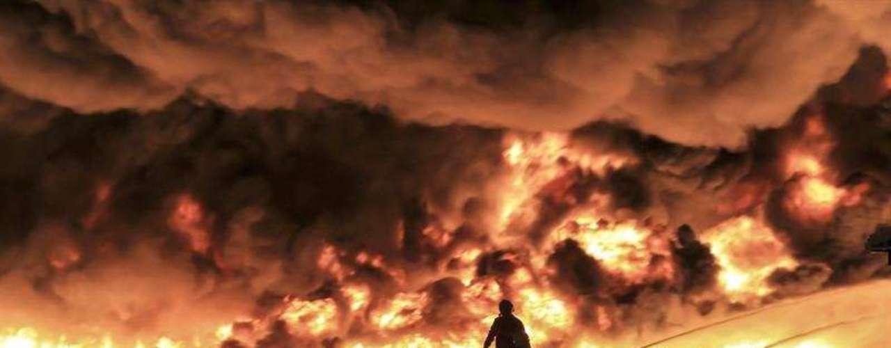 Fotografía facilitada por el Cuerpo de Bomberos de West Midlands, que muestra a un grupo de bomberos mientras lucha por extinguir un incendio en la planta de reciclaje J & A Young, en Smethwick, Reino Unido, el 1 de julio de 2013.