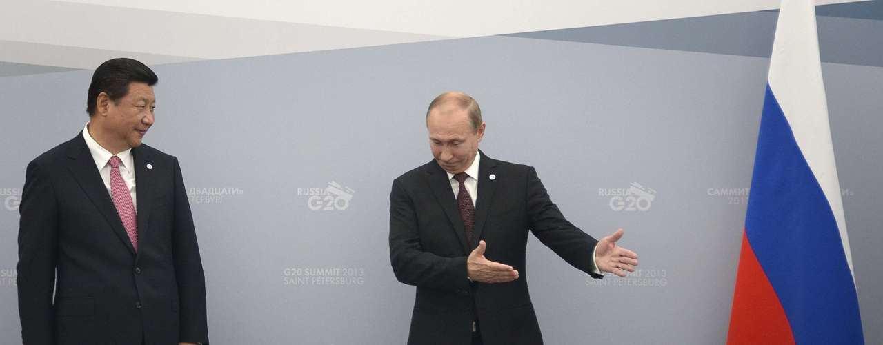 Russia's President Vladimir Putin (R) shows the way to his Chinese counterpart Xi Jinping during a meeting at the G20 Summit in Strelna near St. Petersburg, September 5, 2013.  REUTERS/Alexander Nemenov/Pool (RUSSIA - Tags: POLITICS BUSINESS)