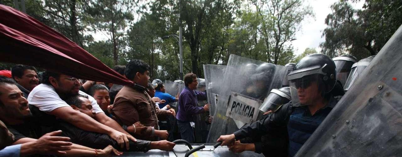 Los manifestantes utilizaron piedras y palos para atacar a los agentes de seguridad, quienes en un primer momento fueron superados en número y cedieron ante la embestida de los profesores.