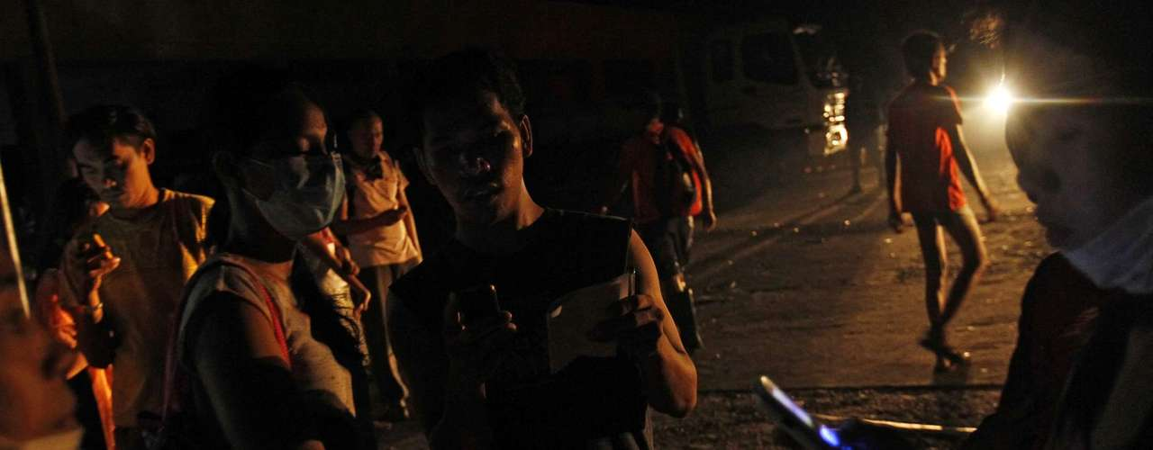 Residents use their mobile phones as night falls after the Super typhoon Haiyan battered Tacloban city in central Philippines November 11, 2013. Mobile networks were partially restored since Sunday. Dazed survivors begged for help and scavenged for food, water and medicine on Monday, as relief workers struggled to reach victims of a super typhoon that killed an estimated 10,000 people in the central Philippines. REUTERS/Edgar Su (PHILPPINES - Tags: DISASTER ENVIRONMENT TELECOMS)