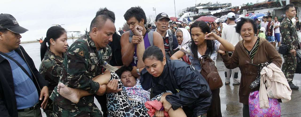 REFILE - CORRECTING SPELLING Military personnel carry a woman after she fainted while waiting in line to leave the town on military air transport, at the destroyed airport after super typhoon Haiyan battered Tacloban City, in central Philippines November 12, 2013. REUTERS/Edgar Su (PHILIPPINES - Tags: DISASTER ENVIRONMENT SOCIETY MILITARY)