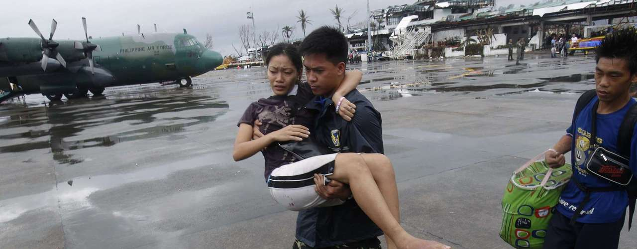A military personnel carries a woman who had injured her leg, to a military C-130 aircraft leaving for Manila, after super typhoon Haiyan battered Tacloban City in central Philippines November 12, 2013. REUTERS/Edgar Su (PHILIPPINES - Tags: DISASTER ENVIRONMENT MILITARY SOCIETY)