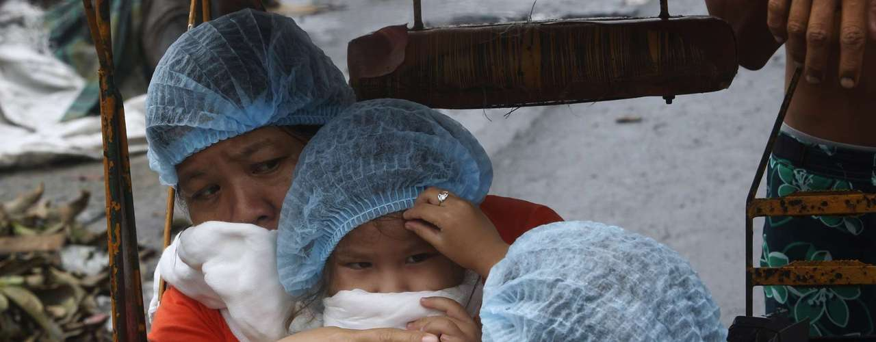 A mother and her two daughters cover their faces with towels as they pass the stench on the road after super typhoon Haiyan battered Tacloban City, in central Philippines November 12, 2013. REUTERS/Edgar Su (PHILIPPINES - Tags: DISASTER ENVIRONMENT SOCIETY)