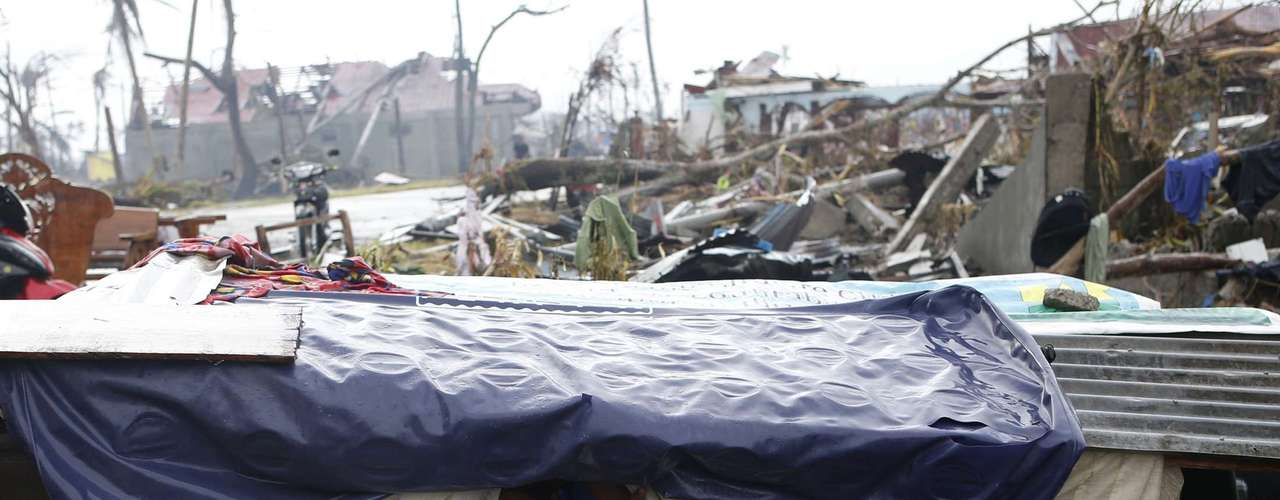 A typhoon victim looks out from a makeshift shelter along a road in Palo, Leyte province in central Philippines, which was battered by Typhoon Haiyan November 12, 2013. Rescue workers tried to reach towns and villages in the central Philippines on Tuesday that were cut off by the powerful typhoon, fearing the estimated death toll of 10,000 could jump sharply, as relief efforts intensified with the help of U.S. military.    REUTERS/Erik De Castro (PHILIPPINES - Tags: DISASTER ENVIRONMENT)