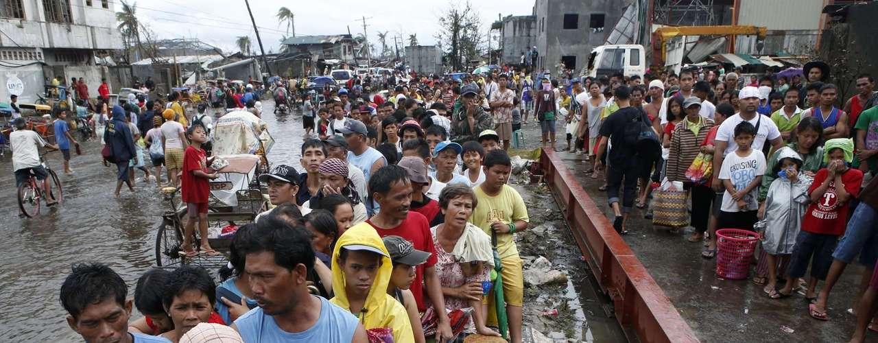 Typhoon victims queue for free rice at a businessman's warehouse in Tacloban city, which was battered by Typhoon Haiyan, in central Philippines November 12, 2013. Rescue workers tried to reach towns and villages in the central Philippines on Tuesday that were cut off by the powerful typhoon, fearing the estimated death toll of 10,000 could jump sharply, as relief efforts intensified with the help of U.S. military.   REUTERS/Erik De Castro (PHILIPPINES - Tags: DISASTER ENVIRONMENT FOOD SOCIETY)