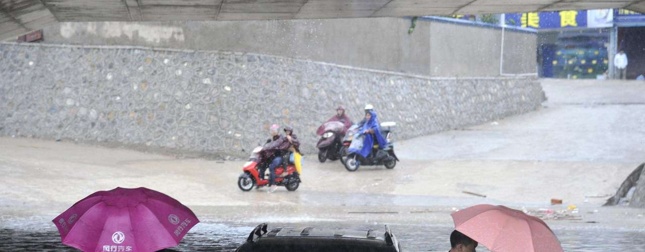 People get out of a stranded car at a flooded underpass amid heavy rainfalls under the influence of Typhoon Haiyan, in Nanning, Guangxi Zhuang autonomous region November 11, 2013. Rainstorms brought by the typhoon hit the south China region on Sunday and Monday, killing at least four, with seven people still missing, according to Xinhua News Agency. Haiyan, one of the most powerful storms ever recorded, killed an estimated 10,000 people in central Philippines, according to officials. Picture taken November 11, 2013. REUTERS/China Daily (CHINA - Tags: ENVIRONMENT DISASTER TPX IMAGES OF THE DAY) CHINA OUT. NO COMMERCIAL OR EDITORIAL SALES IN CHINA