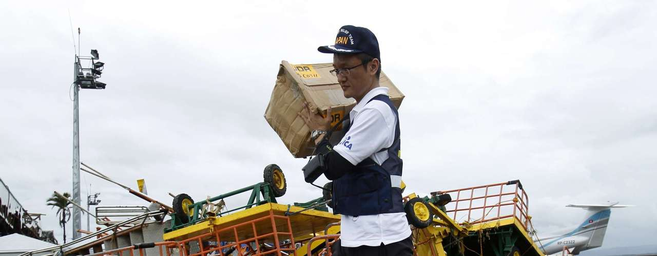 A member of Japan's Disaster Relief Team moves supplies upon arriving at the destroyed airport after Typhoon Haiyan battered Tacloban city in central Philippines November 12, 2013. Rescue workers tried to reach towns and villages in the central Philippines on Tuesday that were cut off by the powerful typhoon, fearing the estimated death toll of 10,000 could jump sharply, as relief efforts intensified with the help of U.S. military.   REUTERS/Edgar Su (PHILPPINES - Tags: DISASTER ENVIRONMENT POLITICS)