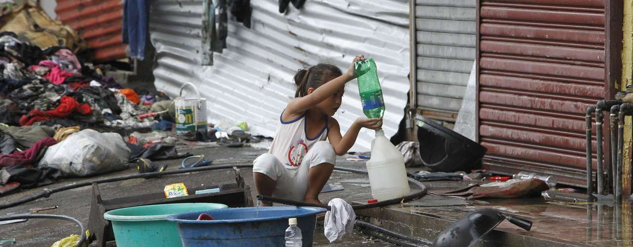 A girl transfers drinking water she collected from a faucet after Typhoon Haiyan devastated Tacloban city, central Philippines November 12, 2013. Rescue workers tried to reach towns and villages in the central Philippines on Tuesday that were cut off by the powerful typhoon, fearing the estimated death toll of 10,000 could jump sharply, as relief efforts intensified with the help of U.S. military.     REUTERS/Romeo Ranoco (PHILIPPINES - Tags: DISASTER ENVIRONMENT)