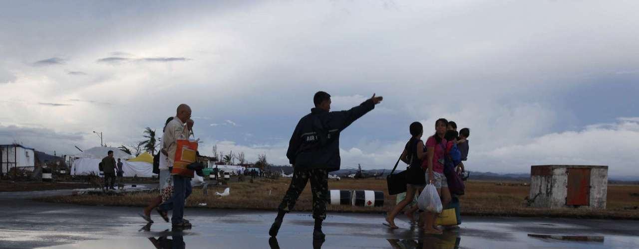 A Filipino soldier gives directions to evacuated Tacloban residents to get onboard a military plane leaving Tacloban airport in central Philippines November 12, 2013. Dazed survivors of super Typhoon Haiyan that swept through the central Philippines killing an estimated 10,000 people begged for help and scavenged for food, water and medicine on Tuesday, threatening to overwhelm military and rescue resources. REUTERS/Bobby Yip (PHILIPPINES - Tags: DISASTER ENVIRONMENT)