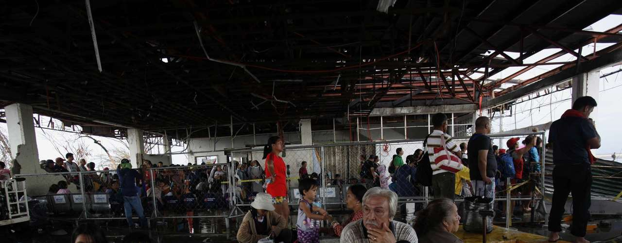 Tacloban residents wait for military flights inside the terminal of Tacloban airport, damaged by Super Typhoon Haiyan, in central Philippines November 12, 2013. A U.S. aircraft carrier set sail for the Philippines on Tuesday to accelerate relief efforts after Typhoon Haiyan killed an estimated 10,000 people in one coastal city alone, with fears the toll could rise sharply as rescuers reach more isolated towns.  REUTERS/Bobby Yip (PHILIPPINES - Tags: DISASTER ENVIRONMENT)