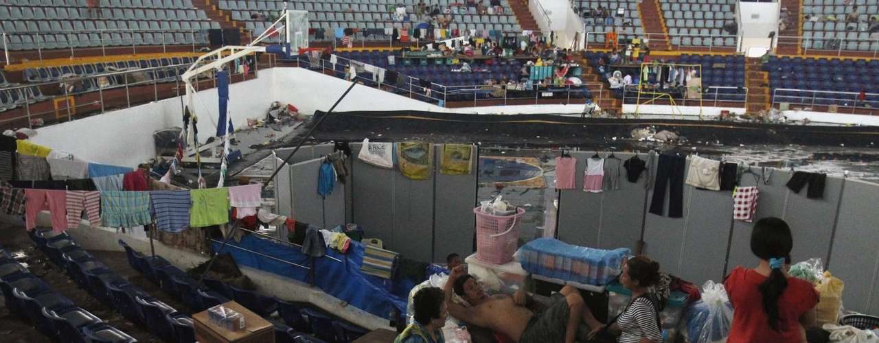 Families take refuge in an indoor basketball stadium at the Tacloban City Convention Center, which has become a homeless shelter after the Super typhoon Haiyan battered Tacloban city in central Philippines November 12, 2013. REUTERS/Edgar Su (PHILPPINES - Tags: DISASTER ENVIRONMENT)