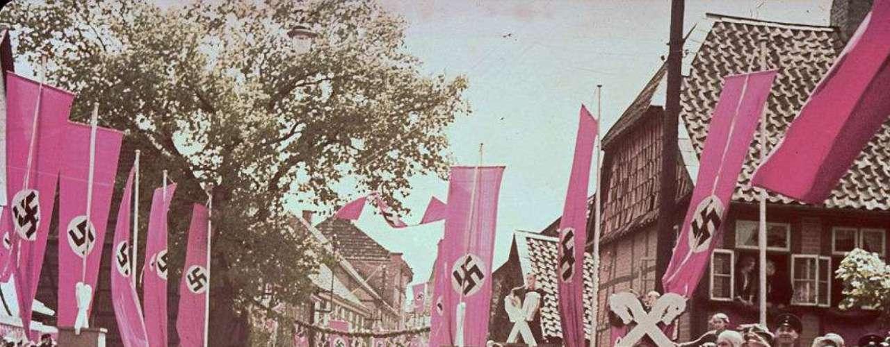 Una multitude Saluda a Hitler y otros oficiales Nazis a su paso por una vía.