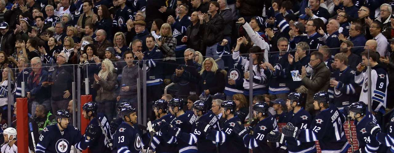 Dec 12, 2013; Winnipeg, Manitoba, CAN; Winnipeg Jets forward Blake Wheeler (26) celebrates with teammates after scoring against the Colorado Avalanche during the first period at the MTS Center. Mandatory Credit: Bruce Fedyck-USA TODAY Sports