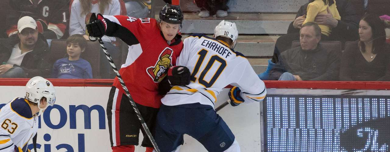 Dec 12, 2013; Ottawa, Ontario, CAN; Buffalo Sabres defenseman Christian Ehrhoff (10) knocks Ottawa Senators left wing Colin Greening (14) off the puck in the third period at the Canadian Tire Centre.The Senators defeated the Sabres 2-1. Mandatory Credit: Marc DesRosiers-USA TODAY Sports