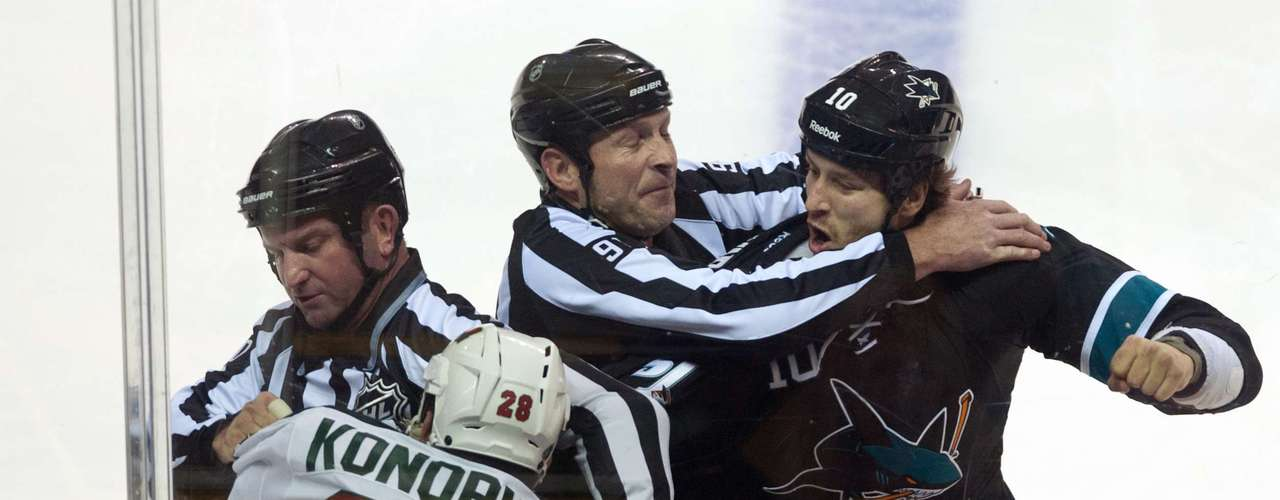Dec 12, 2013; San Jose, CA, USA; Minnesota Wild center Zenon Konopka (28) and San Jose Sharks center Andrew Desjardins (10) are separated by the referees during the first period at SAP Center at San Jose. Mandatory Credit: Ed Szczepanski-USA TODAY Sports