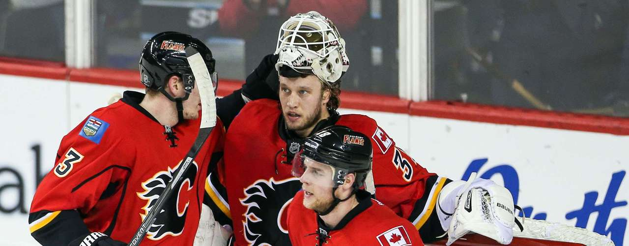 Dec 12, 2013; Calgary, Alberta, CAN; Calgary Flames goalie Karri Ramo (31) get congratulated by Calgary Flames defenseman Ladislav Smid (3) and center Matt Stajan (18) for stopping a penalty shot by Carolina Hurricanes left wing Jeff Skinner (not pictured) during the third period at Scotiabank Saddledome. Calgary Flames won 2-1. Mandatory Credit: Sergei Belski-USA TODAY Sports